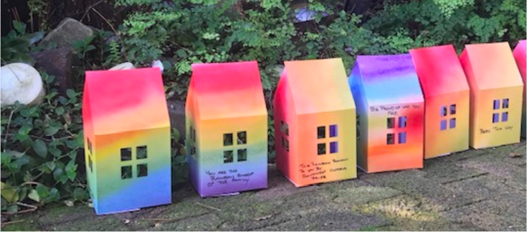 A line of rainbow paper houses made for the Warm Safe Homes Campaign.
