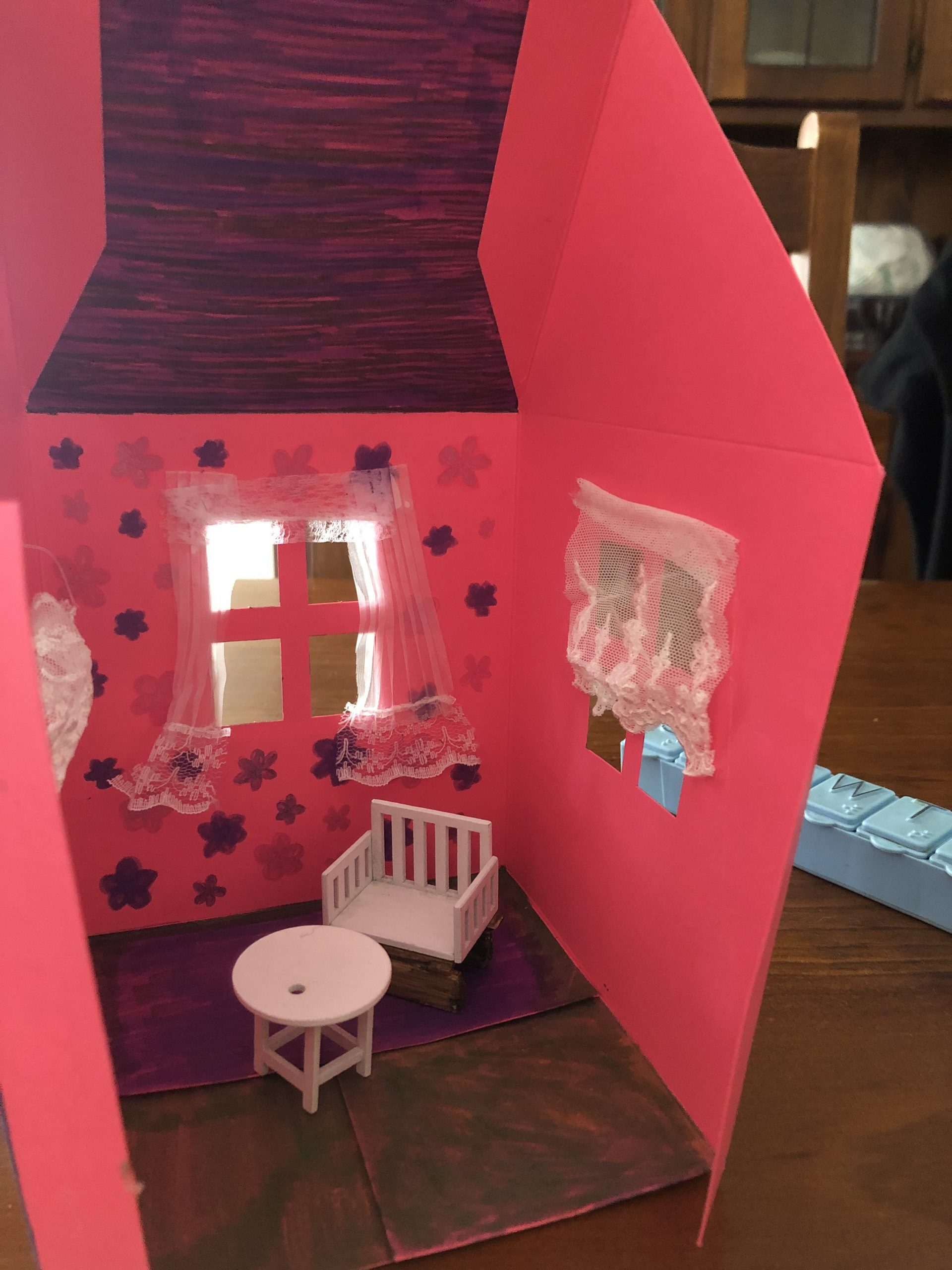 A red warm safe home interior with a chair and table and curtains at the window and decorative walls.
