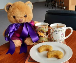 A teddy bear wearing a purple ribbon beside a cup of tea and a plate of biscuits