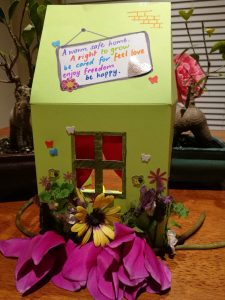 A green warm safe home made of cardboard decorated with flowers and the words 'A warm safe home. The right to grow, be cared for, feel safe, enjoy freedom, be happy.'