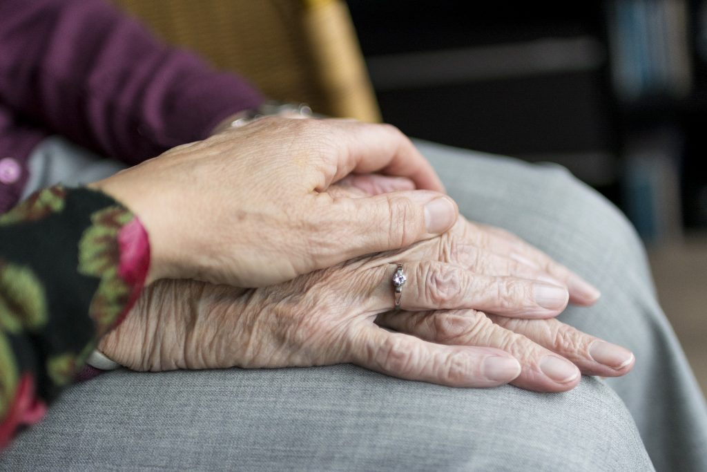 One older person's hand reaching out to rest upon another older person's clasped hands wearing a wedding ring.